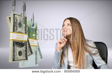 Businesswoman looking at bundle of money