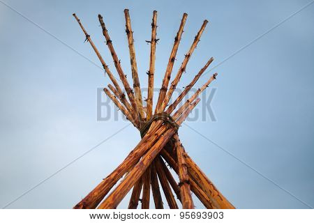 Tipi on blue sky background (Tipi - structure in shape of cone, which is based on multiple poles).
