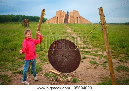 Girl stands near gong and ziggurat in open-air museum at summer