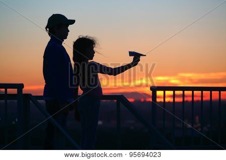 brother and sister let paper plane from roof of multistory home late at night, silhouettes