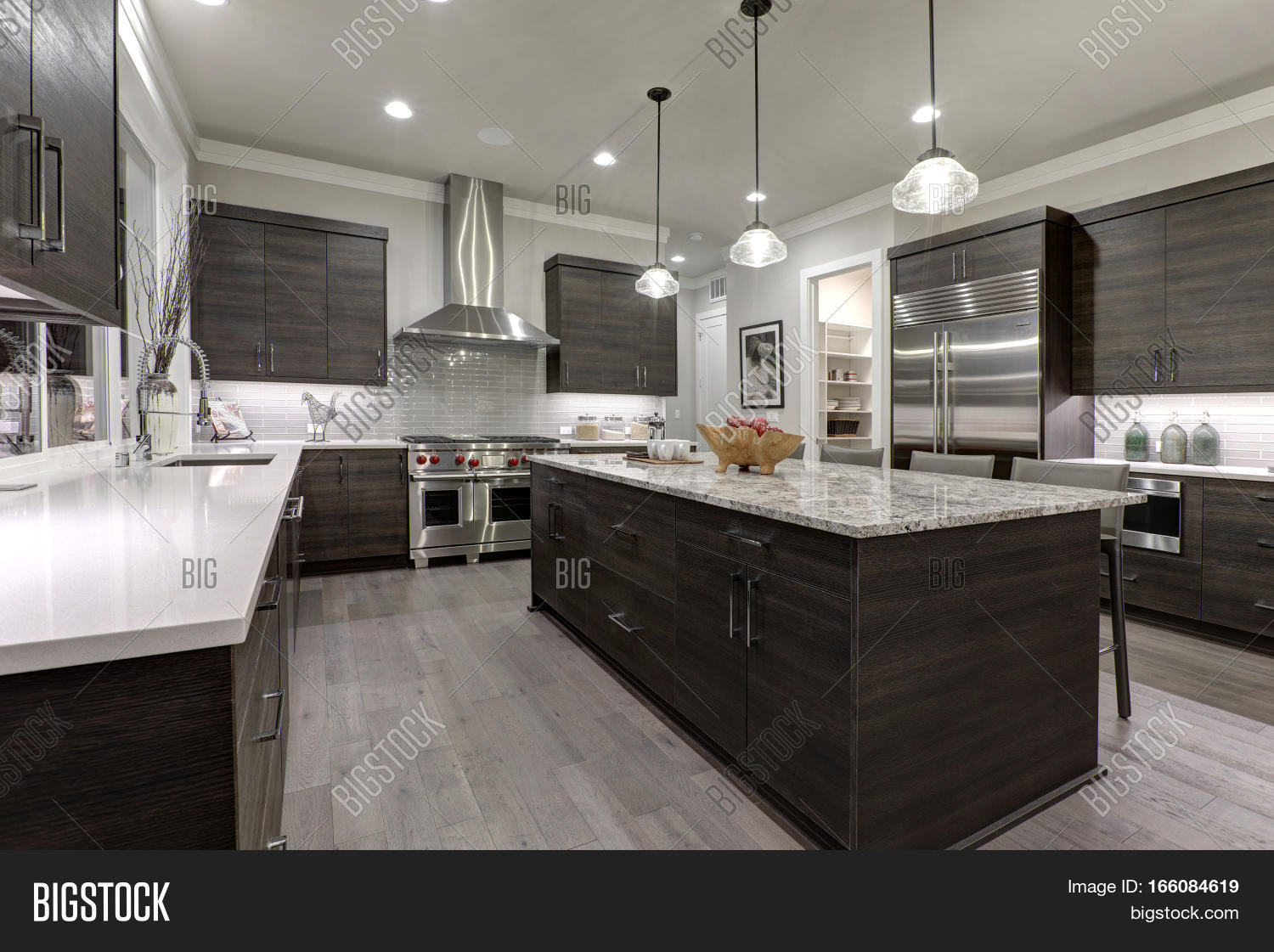Modern Open Plan Gray Kitchen Features Dark Gray Cabinets Paired With  Granite Countertops. Open Door