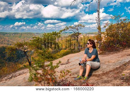 Woman resting after mountain hiking and enjoying view of Red River Gorge in Kentucky.