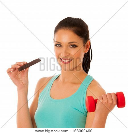 Woman Holding Red Dumbbell After Workout In Fitness Gym Eating Protein Bar Isolated Over White Backg