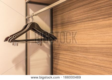 clothes hanger in the wardrobe with warm light