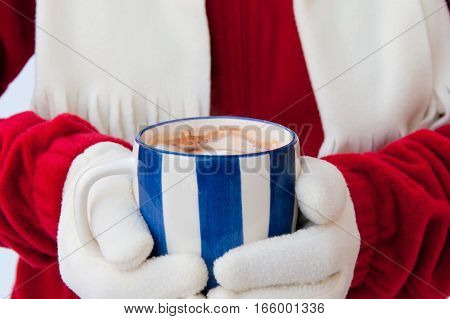 Close up midriff photo of a woman in warm gloves holding cup of hot chocolate with marshmallows at winter. selective focus