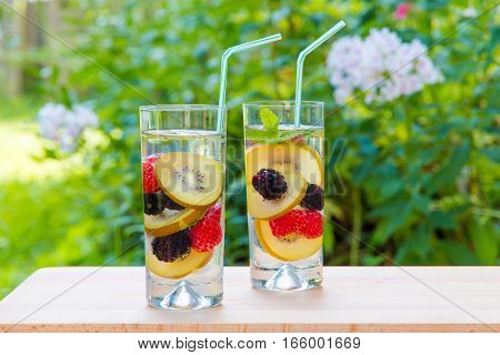 Two glasses of delicious refreshing drink. Infused water with berries golden kiwi and mint.