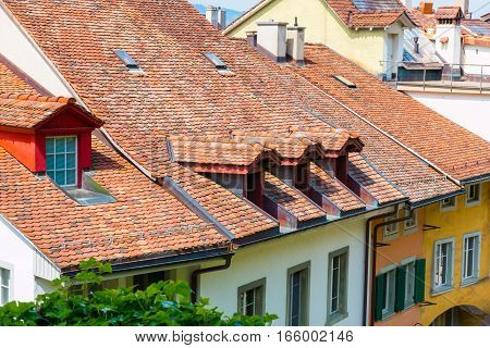 View of red tile roofs and dormer windows on old historical houses in Thun city Switzerland.