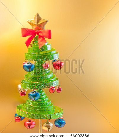 Christmas tree with jingle bells. Golden background with copy space for text.
