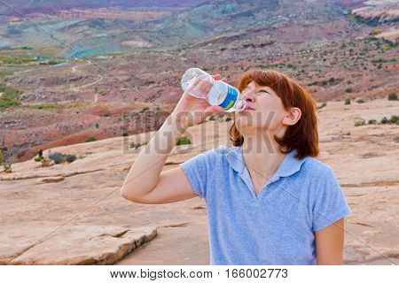 Final sip of water in a bottle. Woman hiker at mountain valley.