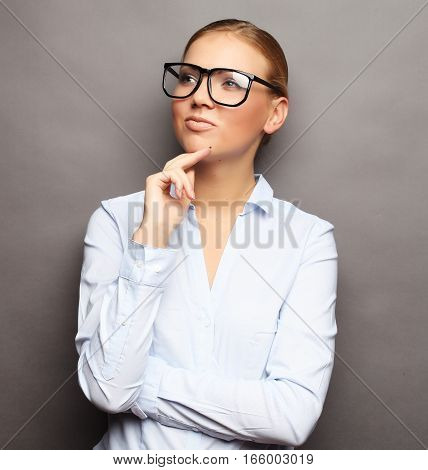 lifestyle, business and people concept: business woman in glasses over grey background