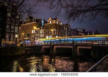 AMSTERDAM NETHERLANDS - JANUARY 08 2017: Trams drives by old bridge in Amsterdam city at night. January 08 2017 in Amsterdam - Netherland.