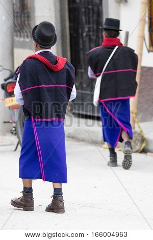 September 6, 2016 Silvia, Colombia: Guambiano men walking in the rain on the street wearing traditional purple skirt
