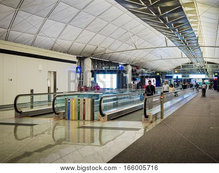 Hong Kong, China - Oct 30, 2016: Inside Hong Kong International Airport. Walking towards departure points Terminal 35 and 36. Image features a mass people-mover escalator.