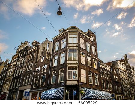 AMSTERDAM NETHERLANDS - JANUARY 10 2017: Famous vintage buildings of Amsterdam city at sun set. General landscape view at tradition Dutch arcitecture. January 10 2017 - Amsterdam - Netherlands.