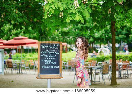Beautiful Young Parisian Woman Reading Menu