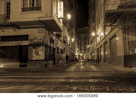 ALICANTE, SPAIN - SEPTEMBER 8, 2016; Alicante Spain gritty street and building scene at night long exposure