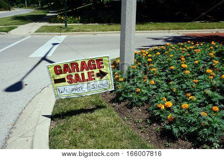 JOLIET, ILLINOIS / UNITED STATES - JUNE 17, 2016: A lawn sign directs people to a garage sale in the Wesmere Estates neighborhood of the Wesmere Country Club.