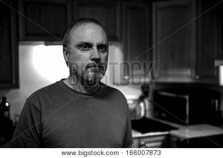 Middle aged man with black eyes and a soulful expression