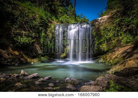 Long Exposure of Oakley Creek Waterfall on a bright Summers Day Auckland New Zealand
