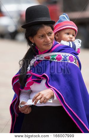 September 6, 2016 Silvia, Colombia: Guambiano indigenous woman dressed in colourful clothing carrying a toddler on her back