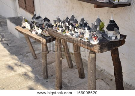 Souvenir of the traditional trulli houses on a wooden bench in Alberobello, Apulia, Italy
