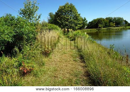 A pathway beside a small, man-made lake in Joliet, Illinois during September.