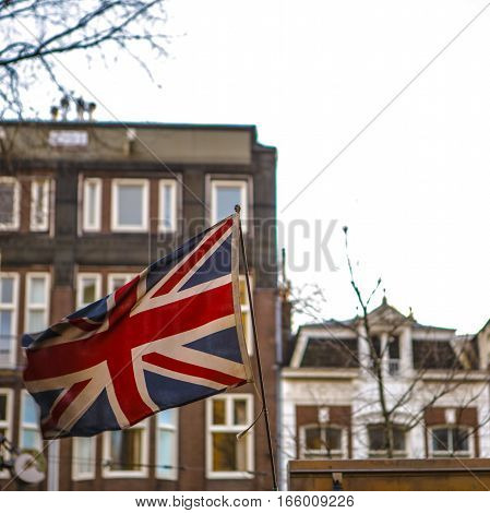 Weathered British flag against traditional buildings. Photo.