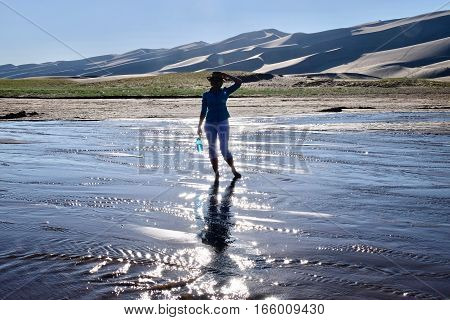 Woman silhouette in shallow river by great sand dunes. Great Sand Dunes National Park and Preserve. Denver. San Luis Valley. Alamosa Saguache County Colorado. United States.