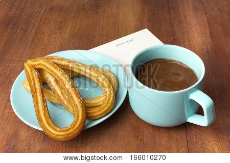 Photo of churros, traditional Spanish, especially Madrid, dessert, in particular for Sunday breakfast. In form of horseshoes, with cup of hot chocolate, on wooden texture with a postcard