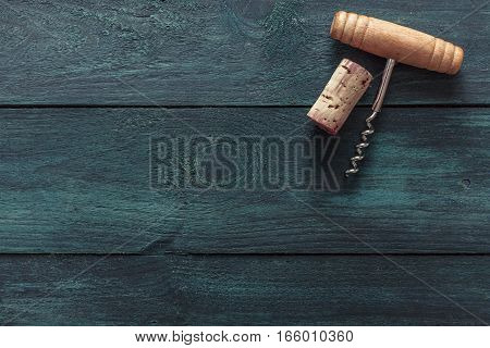 A photo of an old-fashioned corkscrew with a cork, shot from above on a dark blue background texture with plenty of copyspace. A design template for a wine list or a tasting invitation