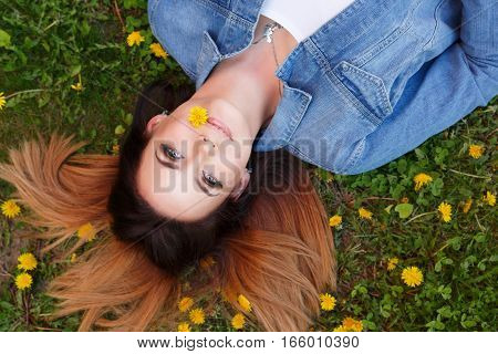 Young attractive girl lies on a lawn among yellow dandelions. She is holding a flower in her mouth. Spring mood.