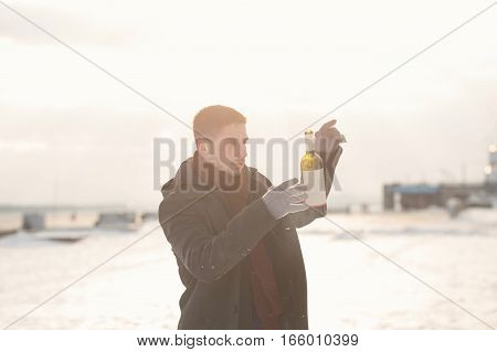 Man walking with a bottle of wine. He is dressed in winter coat scarf and gloves. Man was drunk. He throws up a bottle.