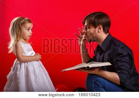 Father and daughter read a book. Girl emotionally reacts to an interesting story. She scared. Tales on roles. The concept of home education.