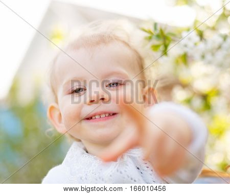Cute little girl shows the index finger at the camera. Spring mood. Soft focus.