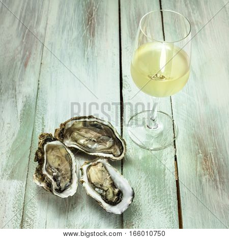 A photo of freshly opened oysters with a slice of lemon and a glass of white wine, on a blurred wooden background texture with copyspace