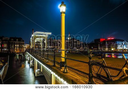 AMSTERDAM NETHERLANDS - JANUARY 12 2017: Old wooden Dutch bridge at night time against rush clouds on January 12 2017 in Amsterdam - Netherlands.