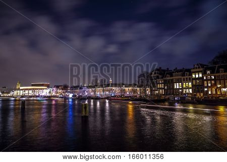 AMSTERDAM NETHERLANDS - JANUARY 12 2017: Beautiful night city canals of Amsterdam with moving passanger boat. January 12 2017 in Amsterdam - Netherland.
