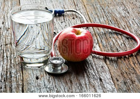 Tools doctor a stethoscope behind an apple and water glass for healthy put on wood table