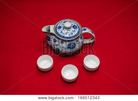 Chinese teapot and white three cup in red background