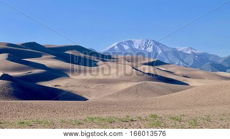 Sand dunes and snowy mountains on the background. Great Sand Dunes National Park and Preserve. Denver. San Luis Valley. Alamosa Saguache County Colorado. United States.