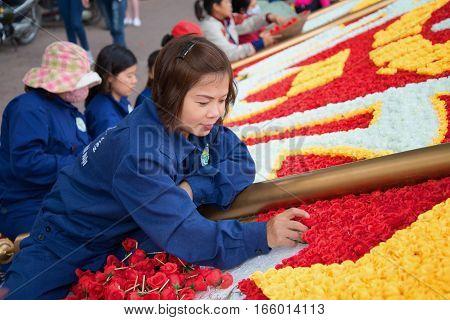HANOI, VIETNAM - JANUARY 11, 2016: Vietnamese girl puts a festive installation of artificial flowers