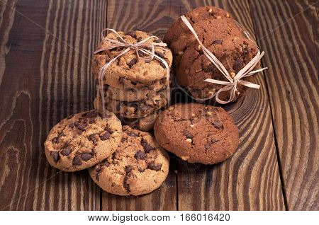 Chocolate cookies tied with ribbon on dark wooden table closeup