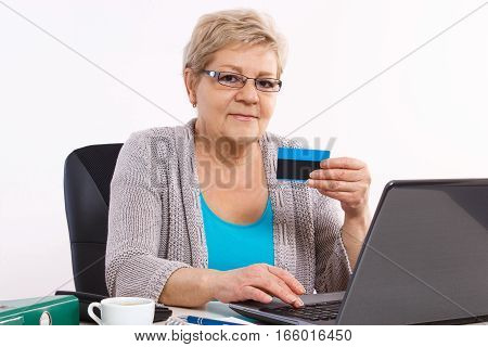 Elderly Senior Woman With Credit Card And Laptop Paying Over Internet For Utility Bills Or Online Sh