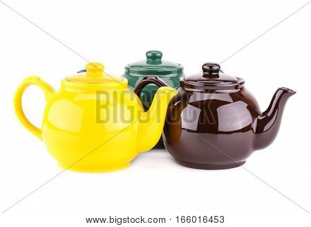 Green yellow and brown teapots isolated on a white background.