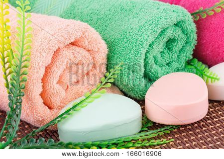 Colorful rolled towels with leaves and soaps closeup picture.