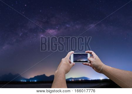Woman hand using smartphone take a photo of the milky way in night sky Landscape of Milky way night sky.