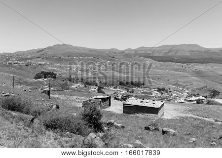 Mountains valley tribal homes in vintage black and white landscape contrasts.