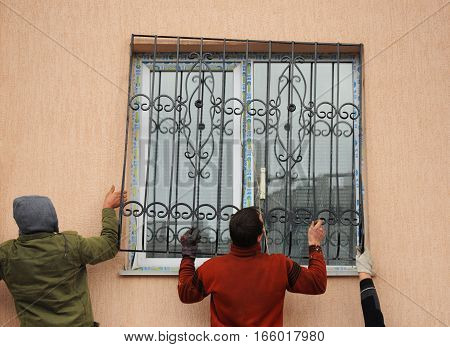 KIEV UKRAINE - JANUARY 23 2017: Close up on window iron security bars installation. Contractors installing iron bars on the new window.