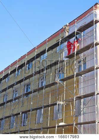 KIEV UKRAINE - JANUARY 23 2017: Builders repair facade thermal insulation. Energy efficiency house wall renovation for energy saving.