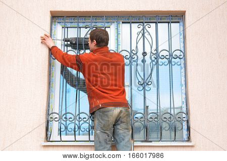 KIEV UKRAINE - JANUARY 23 2017: Worker install window iron security bars for house safety. Contractor installing window iron security bars with drilling machine.